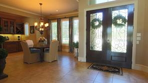 Double doors with leaded glass and wrought iron inserts suggest the grandeur of the interior.  Though the dining table is shown in it s smallest form, there s plenty of room to add a couple of leafs and seat 10 or 12 guests.