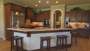 "Full wrap-around breakfast bar reveals a kitchen layout with the ideal ""chef s triangle."""