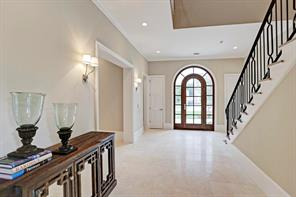 [Foyer]The light-filed foyer has an 11-foot ceiling that expands to the open stairwell s double-height ceiling. Palladian-style front door; travertine tiled floor; custom iron balustrade.