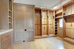 [Master Closet 2]A pair of custom-fitted closets completes the master suite. This one offers rick paneling, track and natural lighting, and a hardwood floor.