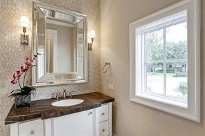 [Powder Bath]Elegant half bathroom appointed with a rich marble deck and stone-tiled wall.