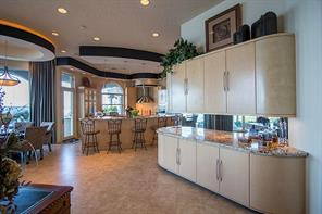 Between the breakfast room and family room, there is an entertainment bar with Kuppersbusch cafe machine and ice maker. The kitchen has easy access to the outside entertainment center at the water s edge.