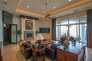 The family room is elegant yet so comfortable. The wall of glass doors opens out on to the patio and Lake Conroe. The designer wrought iron door with vineyard detail leads to the wine grotto.