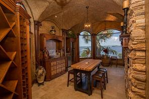 This amazing wine grotto is a recent addition. The fireplace wall is petrified wood. The intricately carved columns support the Italian vaulted ceiling. There s a wine cooler and sink.  There is access to the outside patio.