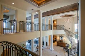 This view of the entry is from the second floor balcony and gives you an idea of the rich detail... curved stairway, wrought iron rails, cantera stone pillars, travertine flooring, gorgeous chandelier.