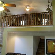 Loft gameroom has barn wood accent wall and hand planed pine wood stairs