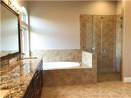 Luxurious master bath featuring double sinks, gorgeous cabinetry, granite counters, garden tub, and glass shower.