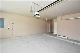 Large, over-sized garage featuring large storage closet, garage door opener, sprinker system control panel, and lots of natural lighting.