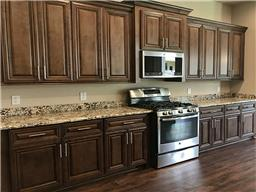 You will love this spacious kitchen featuring beautiful cabinetry, granite counters, and stainless steel appliances,