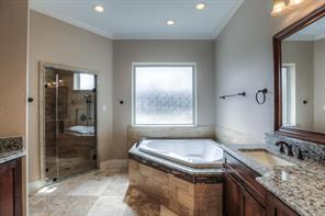 Master bath w/double vanities, oil-rubbed bronze fixtures, travertine flooring, granite counters and granite in shower entry/around tub.