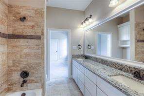 Extra jack&jill bath with double sinks, oil-rubbed bronze fixtures, granite counters, travertine flooring.