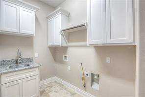 Functional utility room has a granite counter/sink, cabinetry and travertine flooring.