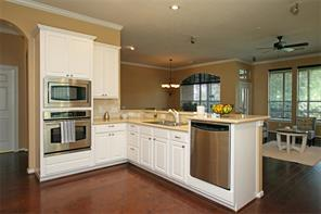 The kitchen also features double ovens, a raised dishwasher, and granite counters.