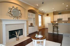 The open concept living room/kitchen features a breakfast bar, fireplace, and built-in cabinets.