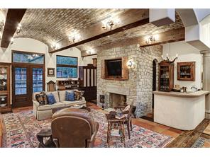Perfect for family gatherings, a stone surround fireplace makes for a warm family room  adorned by a thin-tile brick barrel vaulted ceiling.  A full service wet bar complete with wine room  accompanies the room.  Note sconces on beams.