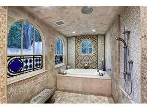 Stain-glass windows provide privacy in this beautiful wet area enhanced by tumbled travertine tiles, custom tiles in bathtub surround  and  decorative mosaic piece.