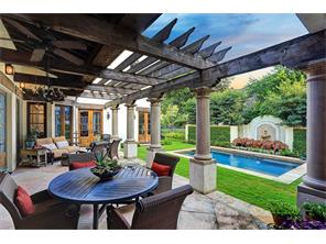 Hand-hewn ceiling beams add character to the veranda with  multiple gathering choices.   Note beautiful landscaping framing pool with fountains.