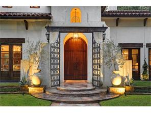 The entrance to this refined European style architecture is enhanced by  custom made iron entry gates, period lanterns, landscape lighting and custom double entry doors.