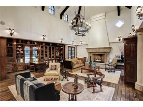 Every detail has been carefully selected and crafted in the double height living room .  Features include beamed ceiling, Brazilian walnut wood floors & hand carved masonry  fireplace. Banks of French doors encompass a commanding view of the garden.