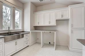 With a laundry room like this laundry may become a fun activity! Note the large sink, ample counter space and lots of built-ins providing excellent organization and storage. Image is of another, similarly constructed property.