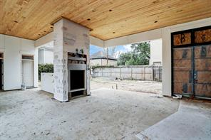 This view from the covered veranda is looking towards the backyard. Note the outdoor fireplace to enjoy on a cool evening and behind the fireplace is the summer kitchen and the doors leads to a bath to serve outdoor entertaining.