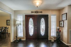 "The welcoming entry has brand new double doors and tile ""wood"" floors."