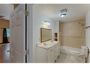 Guest bath features double sinks, tile detail and tub with shower.
