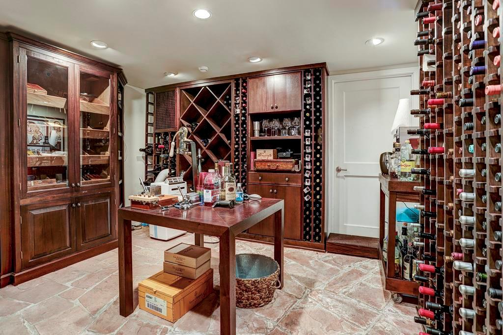 Climate-Controlled Wine Vault (12  x 10 ) with 3 walls of built-in wine bottle storage racks for individual and bulk storage; Humidor Cabinet with programmable humidity levels & display shelves on each side of double glass doors; flagstone flooring