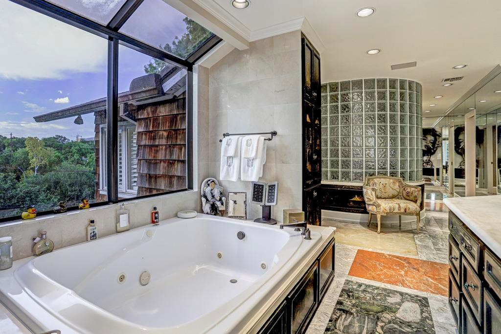 Master Bath - Recessed windowed alcove for oversized Jason Jacuzzi whirlpool tub set into marble deck, with chinoiserie painted base and skylight above; Two designer basins and THG Paris fixtures set into slab marble counter; mirrored accent walls