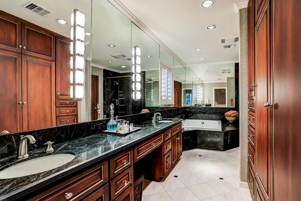 This luxurious marble bath adjoins the secondary bedroom with ceiling-mounted draperies for a queen-sized bed;. two white basins; built-in wardrobe; corner oversized Jason whirlpool tub set in marble deck and marble-tiled shower with glass door