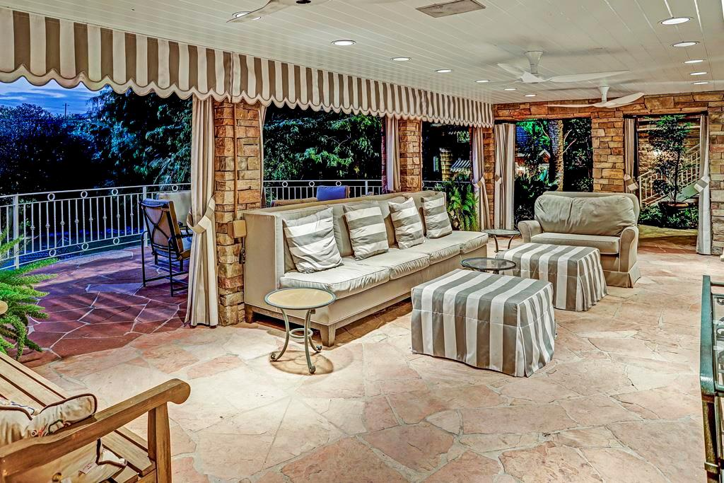 Rear Covered Porch - 28  x 14 :Stacked-stone columns and accent walls; exterior draperies and scalloped awning valance; space for outdoor furniture; wall mount for flat screen TV; flagstone flooring and open to semi-circular terrace balcony