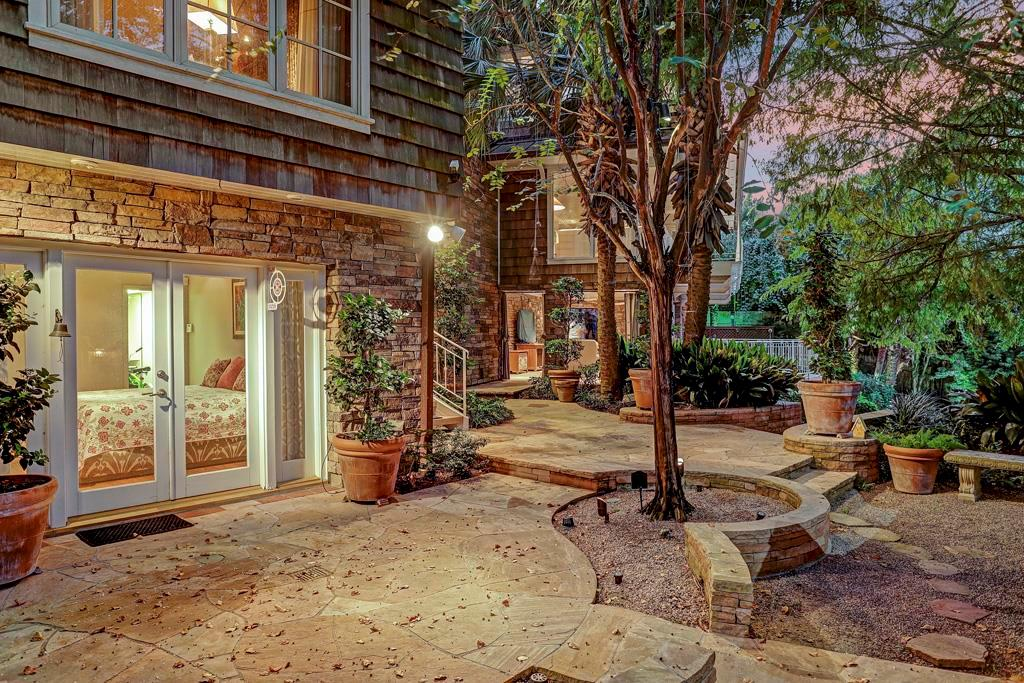 Entrance to the ground level Quarters / Guest Room / Play Room / Exercise Room with its exterior entrance independent of the home; flagstone terrace bordered by palms and planting beds with building, landscape and and accent lighting; stairs to pool