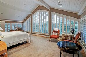 Master Bedroom - 28  x 15 : Peaked ceiling to 13  and three walls of seamless glass windows with plantation shutters; crown molding conceals cove lighting; wide plank hardwood floor; concealed corner marble Coffee / Juice Bar  with SubZero fridge