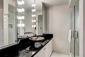 Bath Room attached to Ground Floor Quarters / Bedroom # 5 / Play Room/ or Exercise Room: Art glass vessel sink with custom fixture and angled vanity mirrors with vertical lighting; glazed subway tile floor and walls; shower with glass enclosure