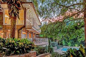 Sunset view of the rear yard facing the home, which sits on just over an acre of land that gently slopes down to Buffalo Bayou. This wide expanse of grassy lawn has been tented for many catered events, some with up to 400 people on the grounds