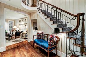 """Foyer - 13  x 10 : Hardwood staircase with wrought iron balustrade; painted-paneled walls with hand-applied artisan glaze and wide-plank hardwood floor with 10"""" extended-height baseboards; cased opening to Living Room and hallway to Mahogany Library"""