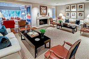Living Room - 24  x 16 : Gas log fireplace with sleek stone mantelpiece; recessed art lighting; fabric upholstered walls; wide-plank hardwood floors and cased opening to Family Room with Wet Bar and balcony overlooking Pool and Pool Terrace below