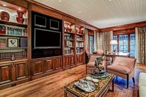 Mahogany Library/Study - 26  x 11 : Three walls of floor-to-ceiling built-ins  with lighted display shelves; space for multiple TV s; space for executive desk; wall-papered ceiling; extended mahogany crown molding cornices conceal drapery hardware