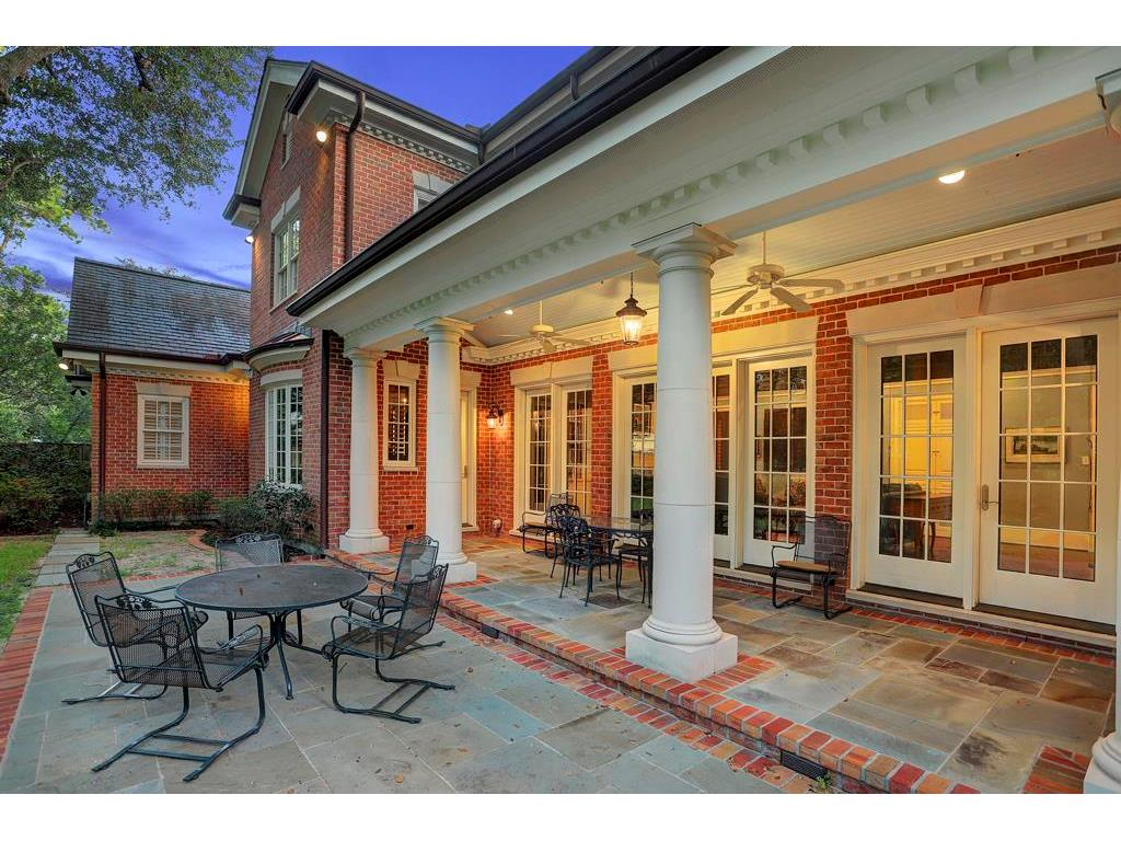 The wide COVERED BACK PORCH will easily accommodate several tables for outdoor dining and entertaining.  Notice the sturdy columns, dental molding & shiplap ceiling of the Porch.  The Porch & Extended Patio flooring is slate bordered with red brick.