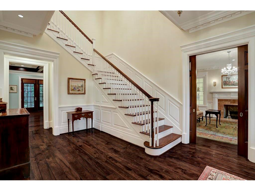 The FOYER showcases the magnificent staircase & gleaming pecan & hickory floors that were crafted by Schenck & Company.  Notice the mahogany pocket doors that frame the Formal Living Room.  You will find 6-panel mahogany doors throughout this home.