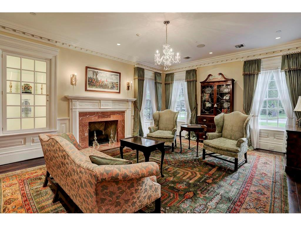 The FORMAL LIVING ROOM is bathed in light from three large divided light windows. The gas-log fireplace with a marble surround & authentically detailed mantel anchor this gracious room.  Notice the lighted curio cabinet with glass shelving.