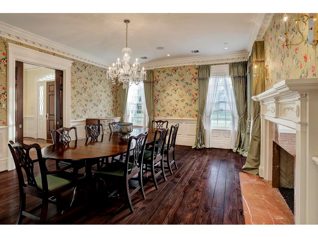 The FORMAL DINING ROOM is across the Foyer from the Formal Living Room and also has a fireplace with a marble surround and intricately designed mantel, a lighted built-in curio cabinet (unseen to the right of the fireplace) and mahogany pocket doors.