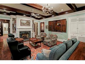 Another view of the FAMILY ROOM with the Wet Bar & built-in TV & stereo cabinet  to the right.  The gas-log fireplace with marble surround and traditional Georgian-style mantel is flanked by built-in bookcases.  Notice the tiered crown moldings.