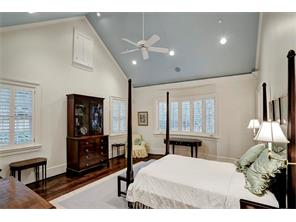 One of the two Master Bedrooms in the MASTER SUITE.  This beautiful room has a cathedral ceiling painted a sky blue, recessed lighting, built-in speakers, a ceiling fan, and multiple shuttered windows, including a gently curved bay window.