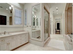 This sumptuous MASTER BATHROOM has 2 travertine-topped vanities, a walk-in shower w/an etched glass door entry & 4 shower heads, travertine floors, a jetted tub w/a travertine surround, 2 private water closets, & large walk-in closets at either end.