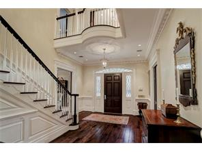 The FOYER welcomes you into this exquisite home with exceptional moldings & millwork throughout.  Notice the 6-panel mahogany front door with divided light side windows & transom, and the pecan & hickory wide-plank flooring.