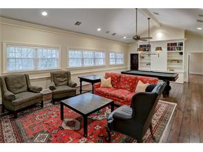 Look at this GAME ROOM with pecan & hickory floors, a cathedral ceiling, recessed lighting & speakers, a wall of windows overlooking the Backyard, a large built-in cabinet for book & game storage & plenty of room for the games of your choice!