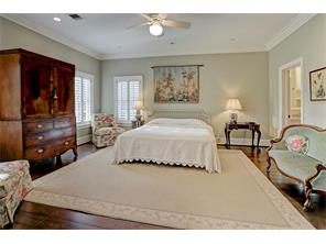 One of the serenely comfortable SECONDARY BEDROOMS with an en suite bathroom, walk-in closet, high ceiling, triple crown molding, and several windows with shutters for natural light.