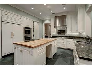 The CHEF S ISLAND KITCHEN has stainless appliances & vent hood, a large side-by-side Sub-Zero refrigerator/freezer, granite counters, two sinks (one in island w/a butcher block top), slate flooring, and plenty of cabinet & drawer storage.