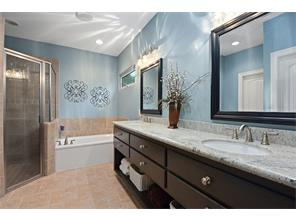 Dark wood vanity with light colored granite and dual sinks make the custom blue paint serene.  Tile floors, walk in master closet and separate shower.
